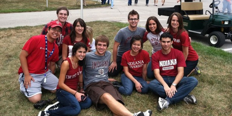 A group of students sitting on a grassy lawn in Indiana University gear, smiling for a photo